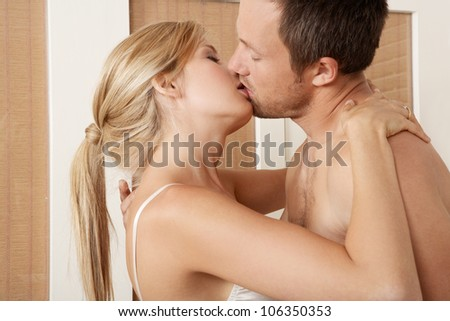 Sexy young couple passionately kissing in bedroom.