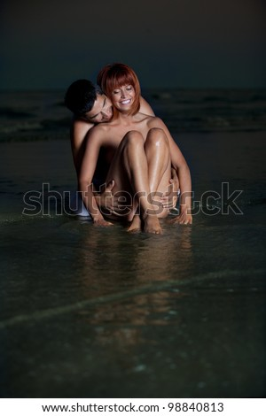 sexy, young couple playing holding each other on the beach, after sunset, smilling
