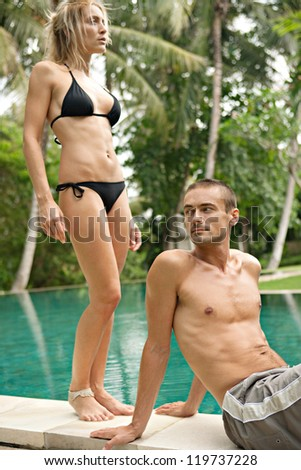 Sexy young couple relaxing by an exotic swimming pool in a tropical destination hotel, outdoors.