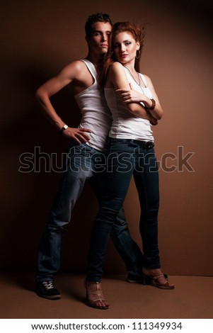 Sexy young couple wearing jeans against in the studio