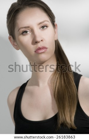 sexy young female model,pony tail,black tank top,serious expression with eye contact,snappy lighting