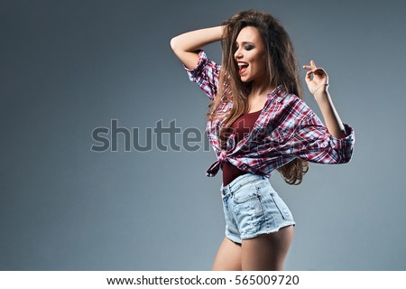 Sexy young girl with disheveled long chestnut hair wearing high waist jeans shorts and oversized knotted red and blue plaid shirt enjoys herself dancing on dark grey background #565009720