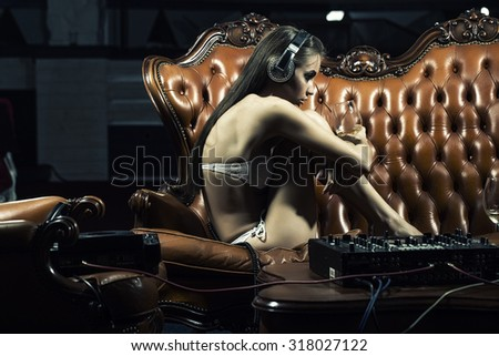 Sexy young glamour dj girl with bright make-up in underwear and headphones sitting on brown leather royal sofa at table with mixer console holding wine glass in night club indoor, horizontal picture #318027122