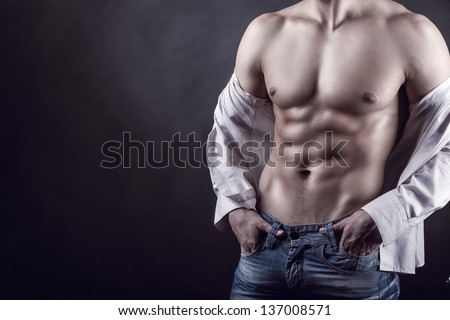 Sexy young man in a shirt with a naked torso on a dark background