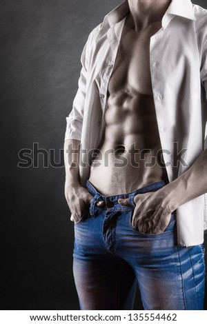 Sexy young man in shirt on a dark background - stock photo