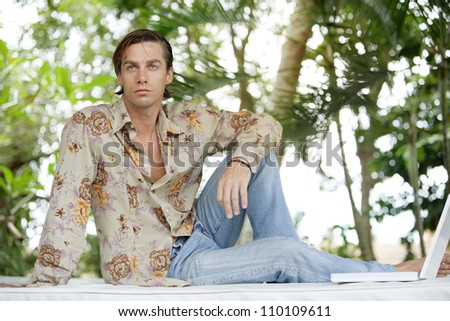 Sexy young man sitting on a outdoors bed in a tropical garden, with his laptop computer.