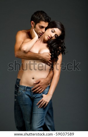 Sexy young multiracial couple in blue jeans having sensual moment