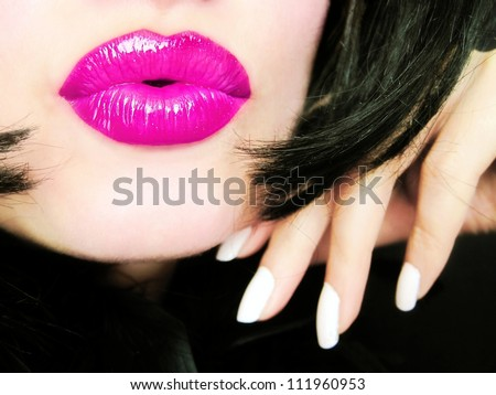 Sexy young pretty woman with pink lips sending a kiss / smooch - closeup