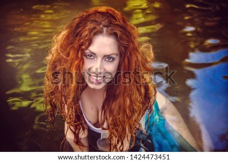 Sexy Young Redhead Woman Sitting in Lake Water #1424473451