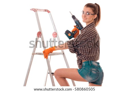60287fdd80 sexy young slim builder girl in glasses makes renovations with drill in her  hands isolated on