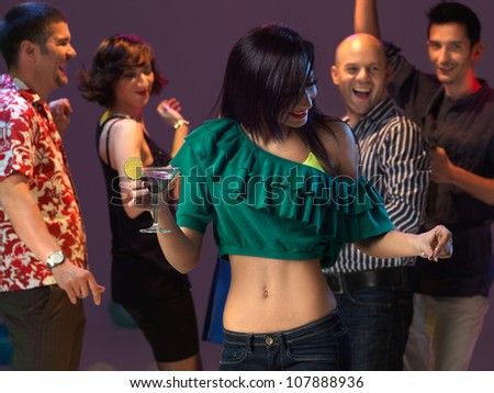 sexy, young woman dancing and drinking a cocktail on the dancefloor, in a night club