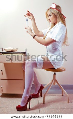 Sexy young woman dressed as a nurse holding syringe
