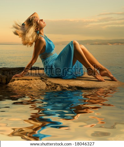 Sexy young woman flapping her blond hair near the ocean - stock photo