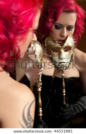 Sexy young woman holding carnival mask in front of mirror