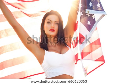 Sexy young woman holding star spangled banner USA flag, 4th of July, Independence day