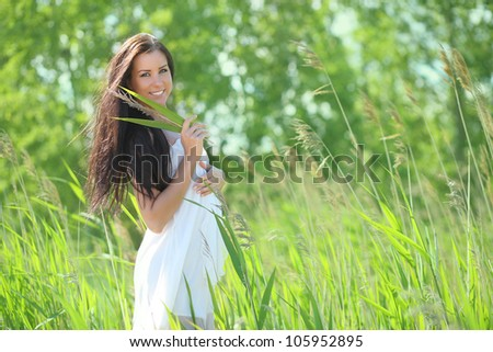 sexy young woman in a white dress in the grass, smiling