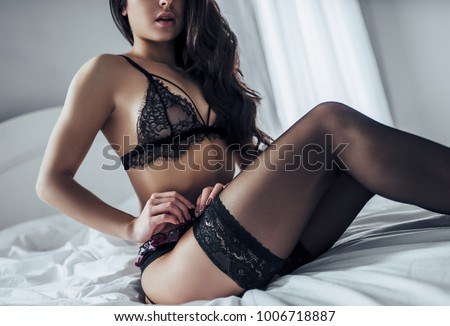 Sexy young woman in black lace lingerie and stockings is sitting in white bed.