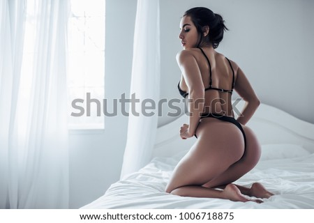 Sexy young woman in black lingerie is sitting on white bed.