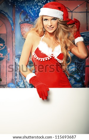 Sexy young woman in Christmas clothes holding white board over Christmas background.