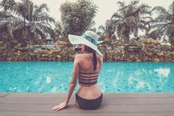 Sexy young woman in hat and sunglasses by the swimming pool. Girl holiday, tan body.