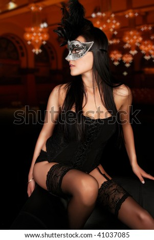 Sexy young woman in lingerie and mask in classic ballroom