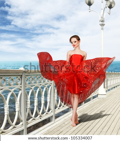 Sexy young woman in long red dress flying under wind walking