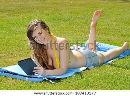 Sexy young woman laying out in the sun in yellow bikini top and shorts reading an e-reader - smiling