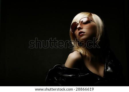 Sexy young woman over black background with moody light