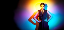 Sexy young woman portrait, on colorful background. Seductive brunette model girl posing in studio in black sexy clothes, fashion accessories, bright makeup in neon light. Clubber, night life concept