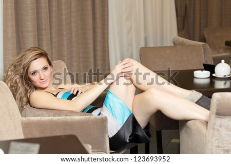 Sexy young woman sitting at a table in cafe