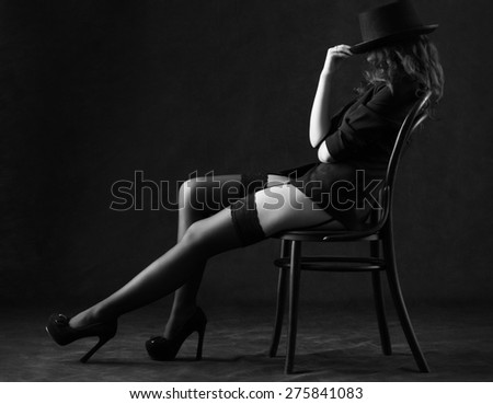 Sexy young woman sitting on a chair on a black background.