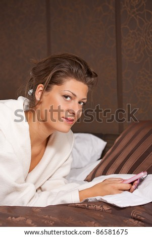 Sexy young woman texting while lying on a bed at home