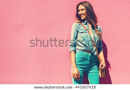 Sexy young woman walking in a city next to pink wall in jeans shirt and mint pants. Fashion summer photo