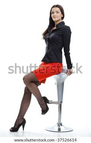 Sexy young woman wearing red skirt and black stockings sitting on bar chair.