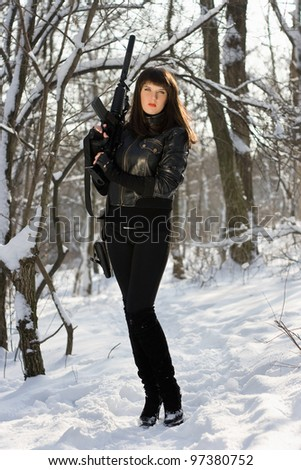 Sexy young woman with a rifle in winter forest
