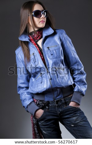 Sexy young woman with blue sunglasses, jeans and leather jacket