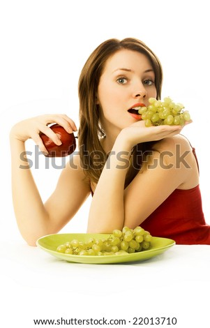 sexy young woman with grapes and an apple sitting by the table