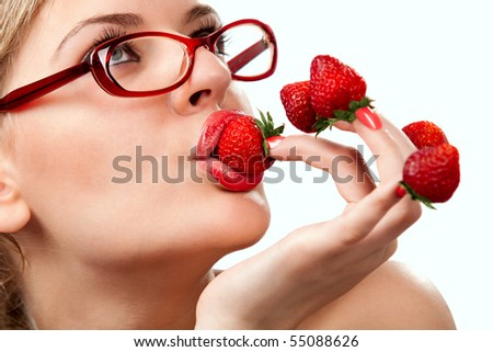 Sexy young woman with red strawberries picked on fingertips isolated on white background