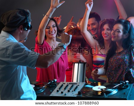 sexy, young women dancing and flirting with the dj in a night club