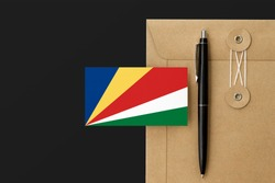 Seychelles flag on craft envelope letter and black pen background. National invitation concept. Invitation for education theme.