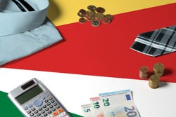 Seychelles flag on minimal money concept table. Coins and financial objects on flag surface. National economy theme.