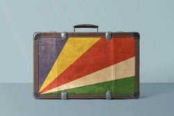 Seychelles flag on old vintage leather suitcase with national concept. Retro brown luggage with copy space text.