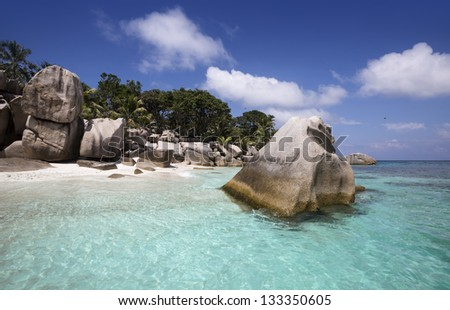 Seychelles. Granite rocks and turquoise sea. White sand and warm water of tropics. Beautiful vacation spot and admiring nature.