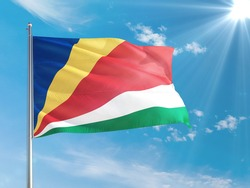Seychelles national flag waving in the wind against deep blue sky. High quality fabric. International relations concept.