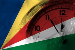 Seychelles, Seychellois flag with clock close to midnight in the background. Happy New Year concept
