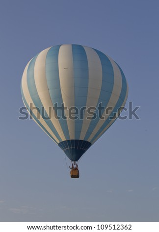 SEYMOUR, WI - AUGUST 3: A White and blue striped hot air balloon high in the sky at the Balloon Rally at the Annual Hamburger Festival on August 3, 2012 in Seymour, Wisconsin.