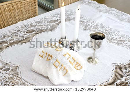 Shabbat eve table with covered challah bread, candles and cup of wine.