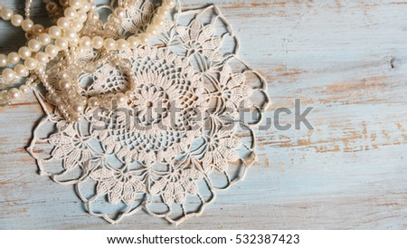 Shabby chic background for wedding with vintage pearl necklaces and lace on old, painted wood background. Top view with copy space.