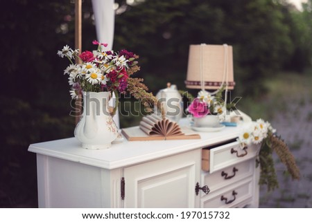 Shabby chic decor, white table with vintage objects on it, flowers vase, flower pot an opened book and a lamp, outdoor