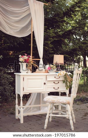 Shabby chic decor, white table with vintage objects on it, flowers vase, flower pot an opened book and a lamp, and a white vintage chair outdoor